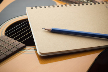 Songwriter guitar and paper