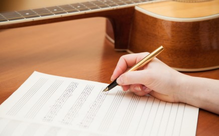 Songwriter with paper and guitar